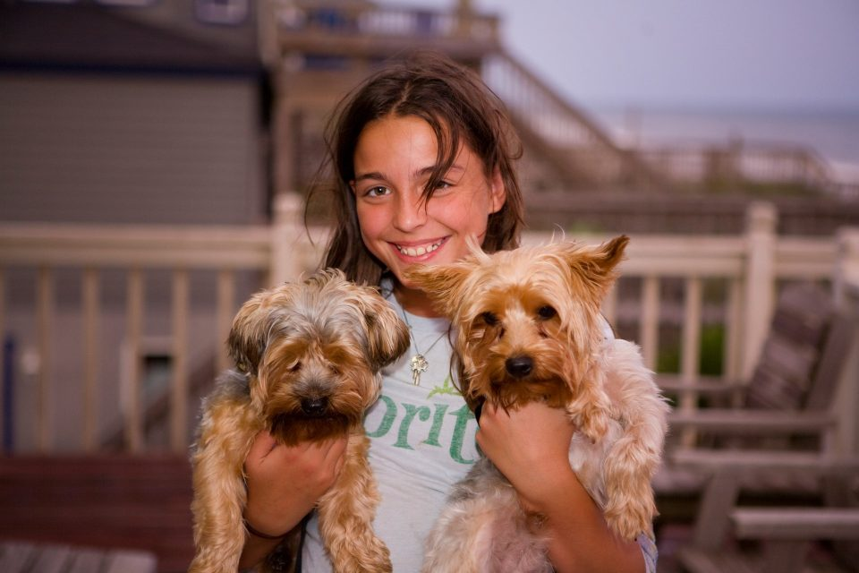 girl holds two dogs